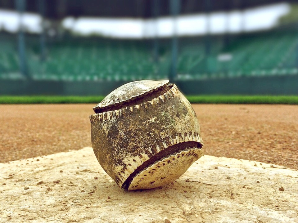 An MLB baseball sitting on home plate.